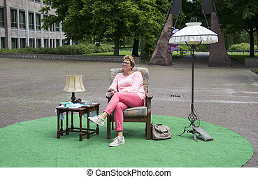 woman sitting in a park on chair with table and lamp