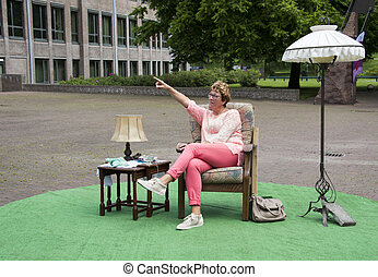 woman pointing to something sitting on chair