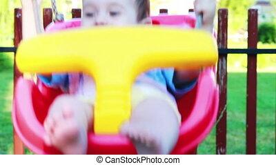 Little baby boy swinging