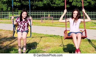 Happy little girls swinging in summer park