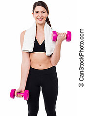 Fitness female instructor lifting dumbbells