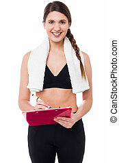 Fit lady trainer preparing diet chart