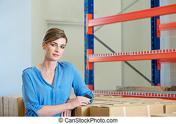 Young female worker standing in warehouse - Portrait of a...