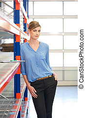 Casual business woman standing in warehouse - Portrait of a...