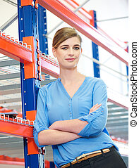 Confident business woman standing in warehouse - Portrait of...