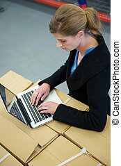Business woman typing on laptop in warehouse - Portrait of a...