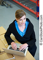 Warehouse employee typing on laptop computer - Portrait of a...