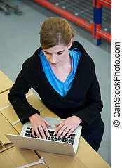 Businesswoman typing on laptop computer in warehouse -...