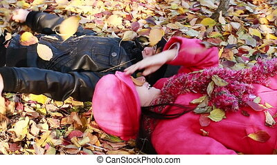 Two girls lying on top of leaves