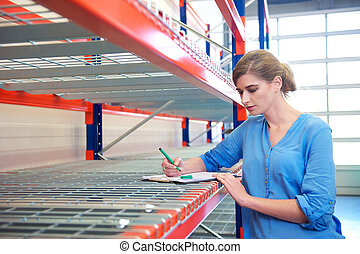 Businesswoman writing inventory on shelves in a warehouse -...