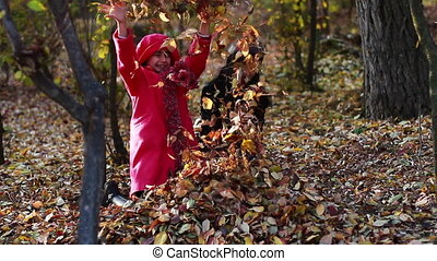 Two girls throwing fall leaves- Autumn