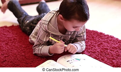 Little boy coloring on floor