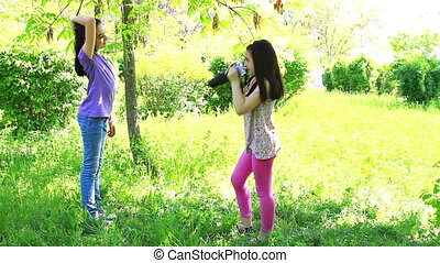 Two girls taking pictures in the city park