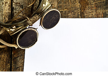 Old welding glasses and white blank paper on wooden...
