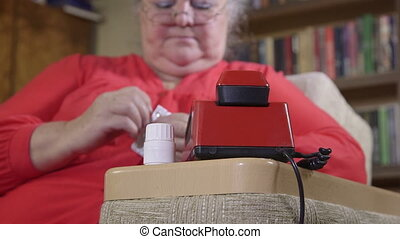 Senior woman taking pills and dials the phone number at...