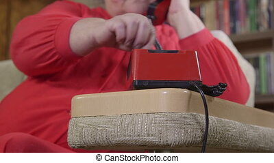 Senior woman using rotary telephone at home