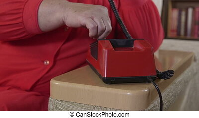 dialing a phone number at home - Senior woman dials the...
