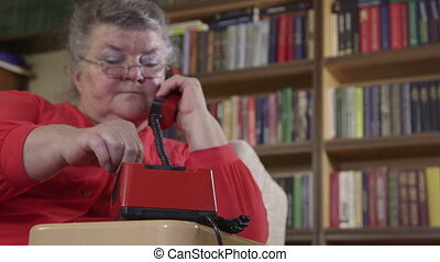 Senior woman using an rotary phone - Senior woman talking on...
