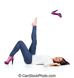 Attractive woman with jeans throwing a fuchsia heel isolated...