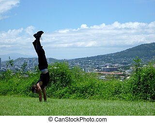 Man wearing sunglass does handstand in grass field
