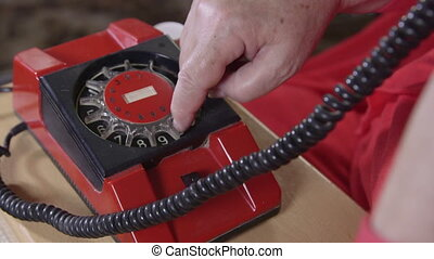 Using an old rotary phone - Senior woman using rotary...