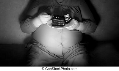 Fat woman watching TV show at night