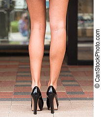 Long legs and high heeled shoes - Partial shot of a tall...