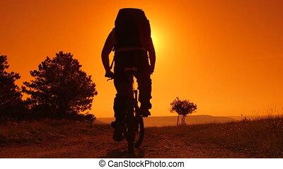 riding mountain bike at sunrise - Traveler riding mountain...