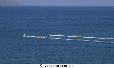 Inflatable banana boats full of tourists speeding away at...