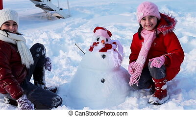 Happy girls with snowman