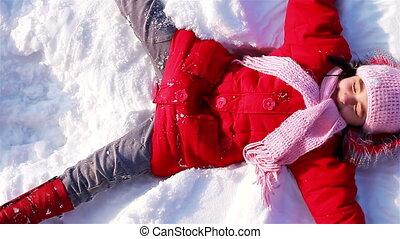 Little Girl makes snow angel