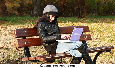 Teenager on bench with laptop