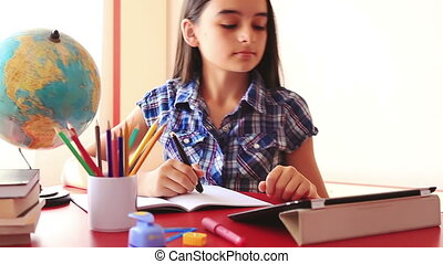 Schoolgirl doing homework - Teenage girl doing homework on...