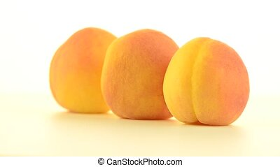 Three peaches rotating on white background.