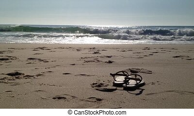 Sandals in sand - Ocean Waves and Beach: The waves from the...