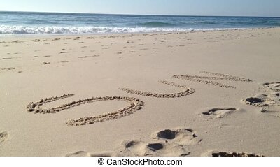 Sun word in sand - Ocean Waves and Beach: The waves from the...