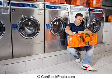 Man With Basket Of Clothes Sitting At Laundromat - Young man...