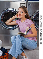 Woman With Book Listening To Music In Laundry - Portrait of...