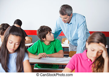 Schoolboy And Teacher Looking At Each Other During...