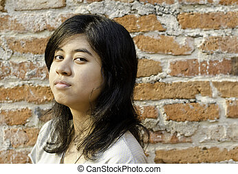 Pretentious girl over brick wall - Pretentious asian girl...