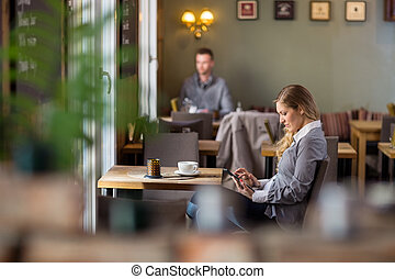 Pregnant Woman Using Digital Tablet At Cafe - Side view of...