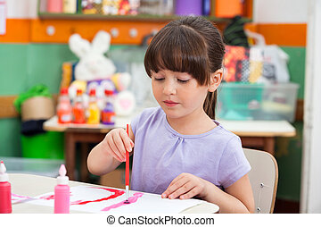 Girl Painting At Desk In Classroom