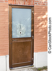door with a bullet hole - cracked door with a bullet hole in...