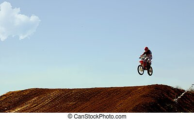 Jumping - Dirt bike rider making a high jump in race.