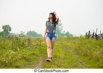 Portrait of pretty brunette walking on farm - Portrait of...