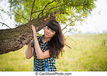 Portrait of pretty brunette holding the trunk in summer...