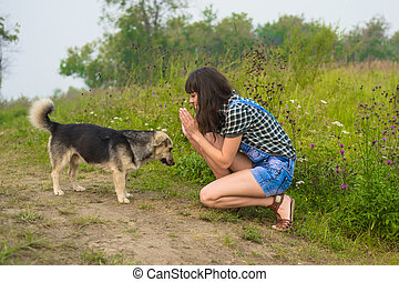 Portrait of pretty brunette playing with dog in summer...