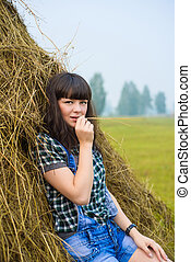 Portrait of pretty brunette lying on haystack in summer...