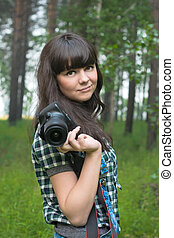 Portrait of pretty brunette taking pictures in summer forest