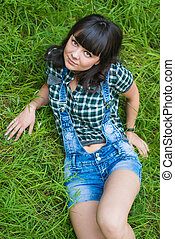 Portrait of pretty brunette lying on grass in countryside